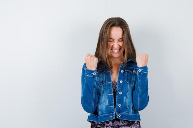 Jeune femme montrant le geste du gagnant en chemisier, veste en jean et l'air heureux, vue de face.