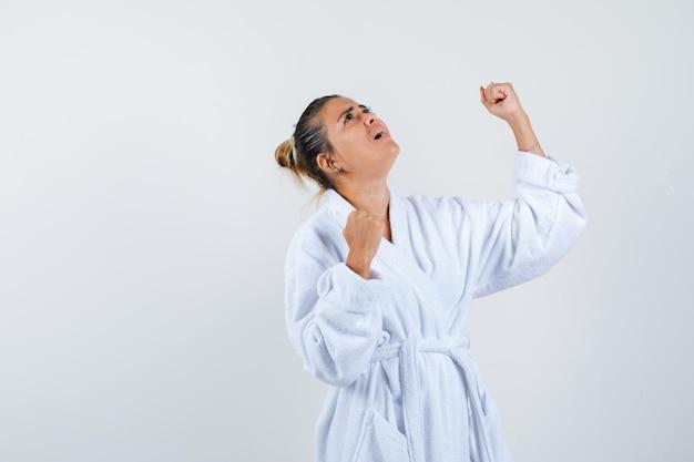 Jeune femme montrant le geste du gagnant en peignoir et à la chance