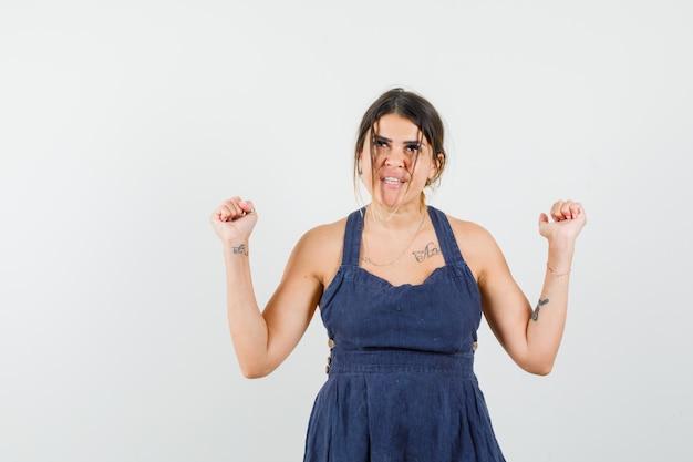 Jeune femme montrant le geste du gagnant en robe et l'air heureux