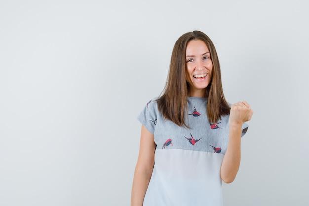 Jeune femme montrant le geste du gagnant en t-shirt et à la béatitude, vue de face.