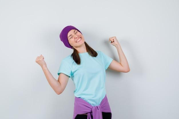 Jeune femme montrant le geste du gagnant en t-shirt bleu, bonnet violet et ayant l'air chanceux. vue de face.
