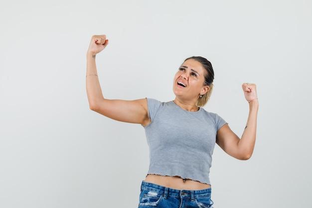 Jeune femme montrant le geste du gagnant en t-shirt, short et à la chance.
