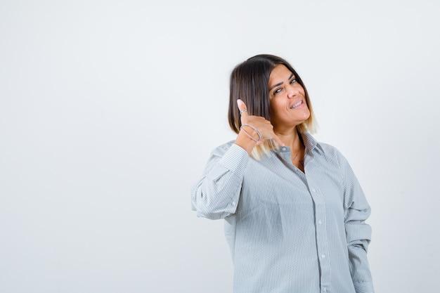 Jeune femme montrant le geste du téléphone en chemise surdimensionnée et l'air confiant. vue de face.