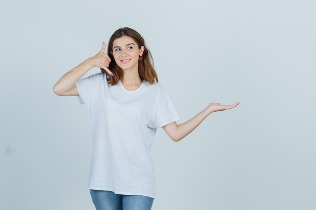 Jeune femme montrant le geste du téléphone tout en faisant semblant de tenir quelque chose en t-shirt, jeans et à la vue de face, confiant.