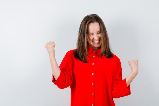 Jeune femme montrant le geste du vainqueur en chemisier rouge et l'air joyeux, vue de face.