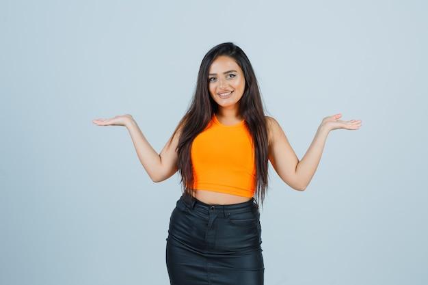 Jeune femme montrant le geste des écailles en maillot, mini jupe et à l'air heureux. vue de face.