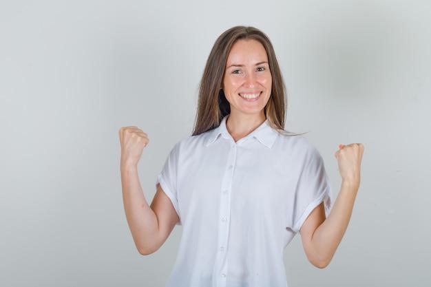 Jeune femme montrant le geste gagnant en chemise blanche et à la recherche de plaisir