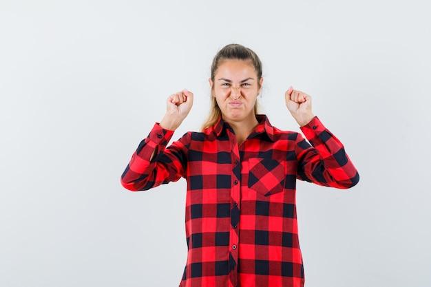 Jeune femme montrant le geste gagnant en chemise à carreaux et à la chance. vue de face.