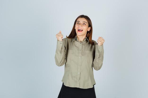 Jeune femme montrant le geste gagnant en chemise, jupe et à la béatitude