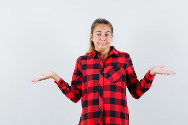Jeune femme montrant un geste impuissant en chemise à carreaux et à la confusion. vue de face.