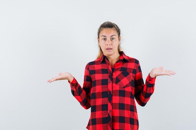 Jeune femme montrant un geste impuissant en chemise à carreaux et à la confusion