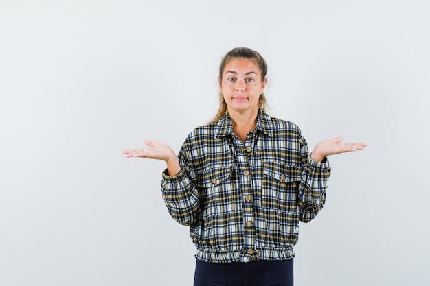 Jeune femme montrant un geste impuissant en chemise à carreaux et à la vue confuse, de face.