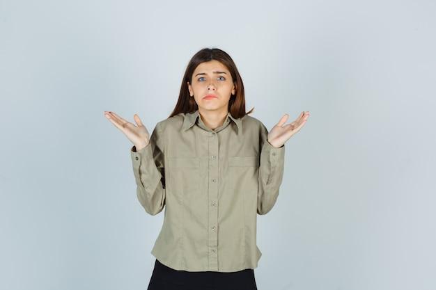 Jeune femme montrant un geste impuissant, courbant les lèvres en chemise, jupe et l'air perplexe, vue de face.