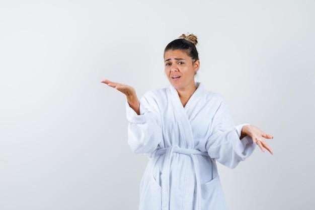 Jeune femme montrant un geste impuissant en peignoir et à la désespérée