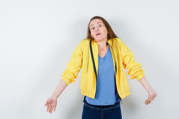 Jeune femme montrant un geste impuissant en t-shirt et semblant confuse. vue de face.