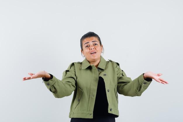 Jeune femme montrant un geste impuissant en t-shirt