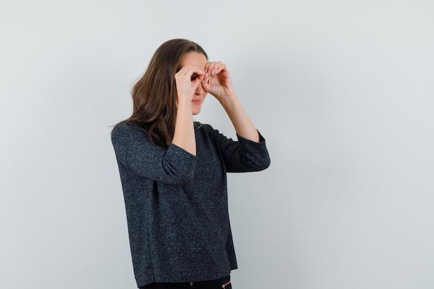 Jeune femme montrant un geste de lunettes en chemise et à la recherche