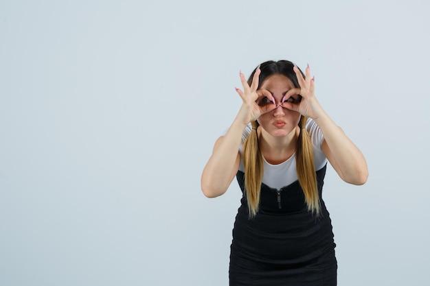 Jeune femme montrant un geste de lunettes et des lèvres boudeuses