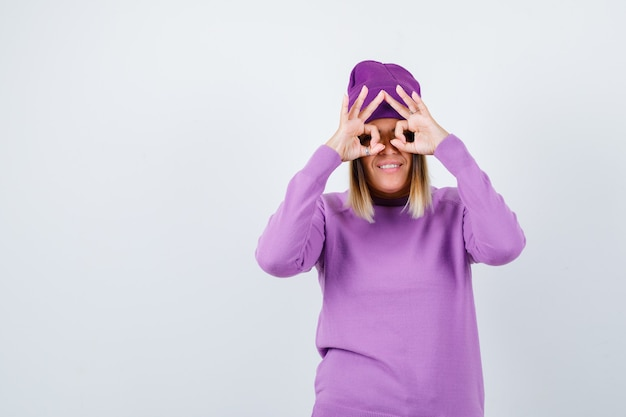 Jeune femme montrant un geste de lunettes en pull violet, bonnet et semblant drôle. vue de face.