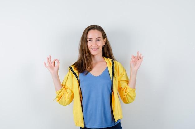 Jeune femme montrant un geste de méditation en t-shirt, veste et semblant joyeuse, vue de face.