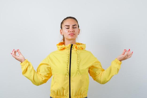 Jeune femme montrant un geste de méditation en veste jaune et l'air détendue. vue de face.