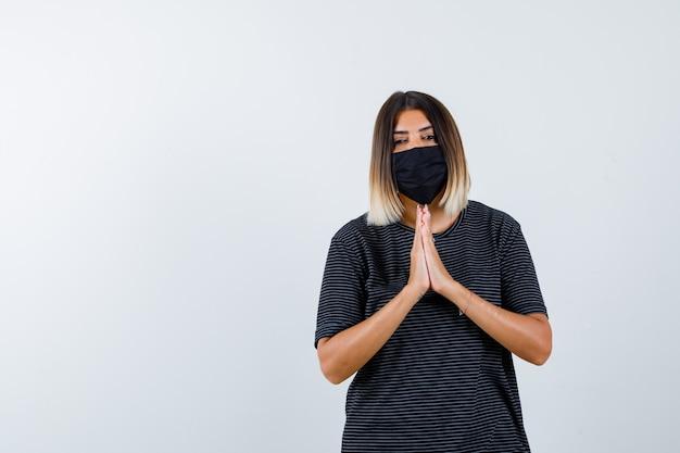 Jeune femme montrant le geste de namaste en robe noire, masque noir et à la recherche de sérieux. vue de face.