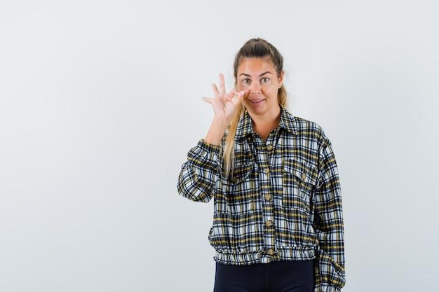 Jeune femme montrant le geste ok en chemise à carreaux et à la gaieté. vue de face.