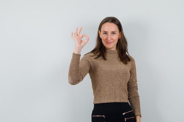 Jeune femme montrant le geste ok en chemisier doré et à la recherche d'optimiste. vue de face.