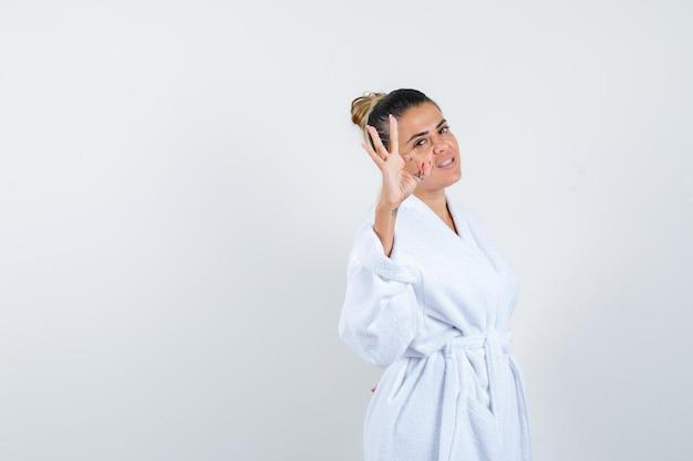 Jeune femme montrant un geste ok en peignoir et à la béatitude