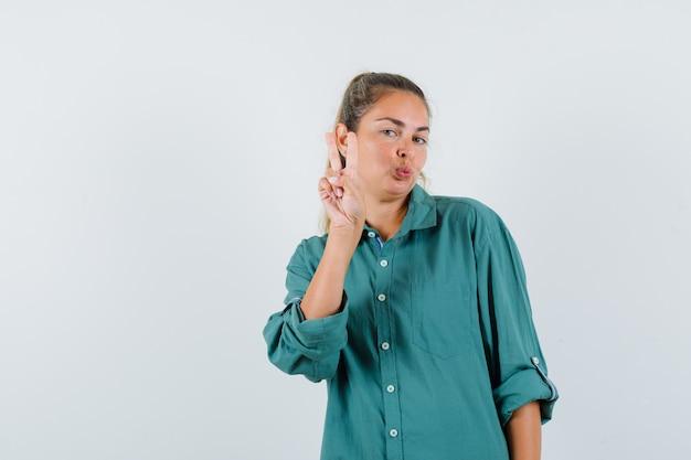 Jeune femme montrant le geste de paix en chemisier vert et à la recherche attrayante