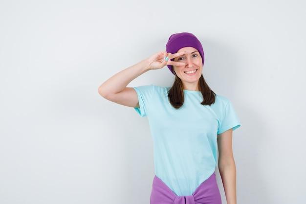 Jeune femme montrant un geste de paix sur l'œil en t-shirt bleu, bonnet violet et regardant jolly, vue de face.