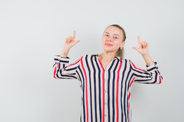 Jeune femme montrant le geste de perdant avec ses deux mains en chemisier rayé et à la belle