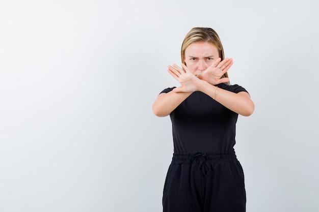 Jeune femme montrant un geste de refus en t-shirt, pantalon et à la grave, vue de face.