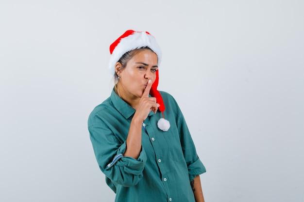 Jeune femme montrant un geste de silence en chemise, bonnet de noel et l'air confiant, vue de face.