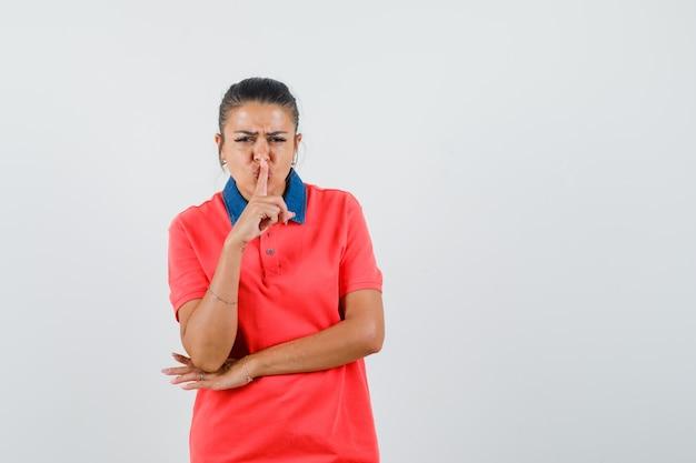 Jeune femme montrant le geste de silence, mettant l'index sur la bouche en t-shirt rouge et à la furieuse, vue de face.