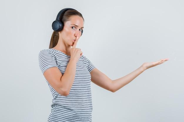 Jeune femme montrant le geste de silence avec paume étendue en t-shirt, casque, vue de face.