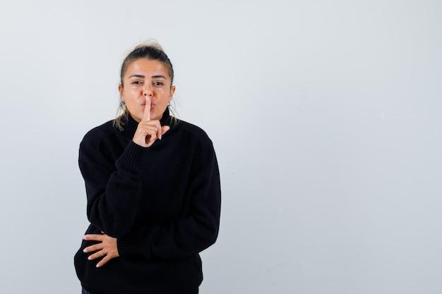 Jeune femme montrant le geste de silence en pull à col roulé noir et à la confiance. vue de face.