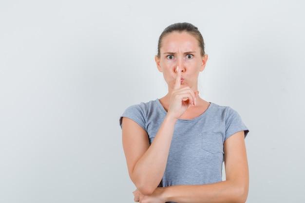 Jeune femme montrant le geste de silence en t-shirt gris et à la recherche de sérieux. vue de face.