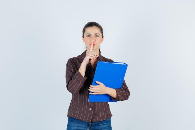Jeune femme montrant un geste de silence, tenant un dossier en chemise, jeans et semblant raisonnable, vue de face.