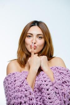 Jeune femme montrant un geste de silence en tricot
