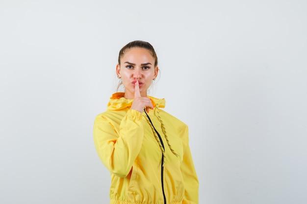 Jeune femme montrant un geste de silence en veste jaune et semblant confiante, vue de face.