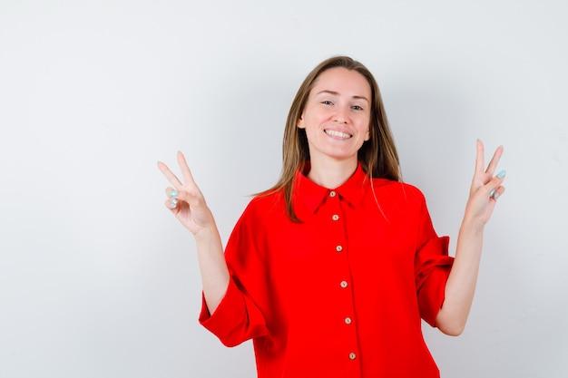Jeune femme montrant le geste de la victoire en blouse rouge et l'air heureux. vue de face.