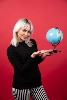 Jeune femme montrant un globe sur fond rouge. photo de haute qualité