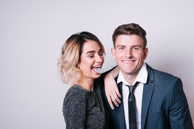 Jeune femme montrant une langue blanche près d'un homme souriant