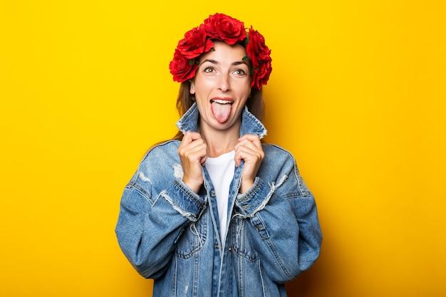 Jeune femme montrant la langue en veste en jean et guirlande de fleurs rouges sur sa tête sur un mur jaune.