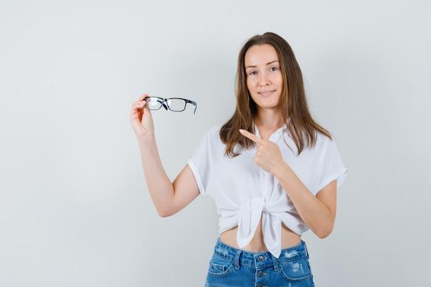 Jeune femme montrant des lunettes en chemisier blanc et à la recherche positive. vue de face.