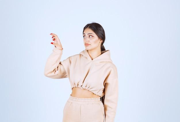 Jeune femme montrant les mesures d'un objet
