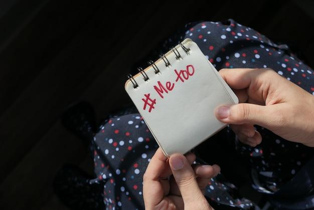 Jeune femme montrant une note avec le texte moi aussi.
