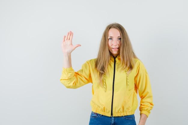 Jeune femme montrant un panneau d'arrêt en blouson aviateur jaune et jean bleu et à la grave, vue de face.