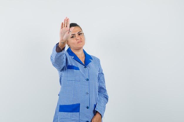 Jeune femme montrant un panneau d'arrêt en chemise de pyjama vichy bleu et à la grave, vue de face.